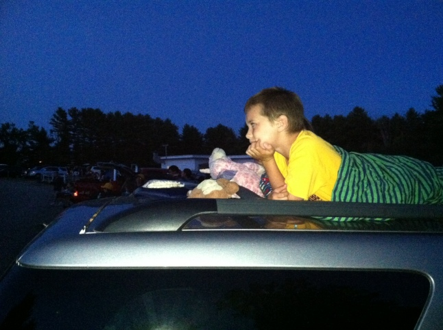 """Perched atop the family car, an MHS staff member's son enjoys the new movie, """"Planes,"""" at the Saco Drive-In recently. Despite a few mosquitos, great fun was had by all--especially the kiddos, who got to stay up past their normal bedtime!"""