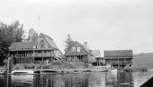 Some of the buildings of the Parmachenee Club, a private hunting-fishing club at Camp Caribou on Treat's Island, Parmachenee Lake, in about 1940. The club was founded in 1890 on the Meadows of the Magalloway River and moved to the island when a paper company dam flooded the first location. MMN# 19385