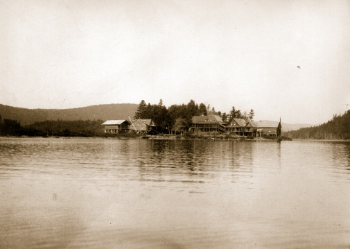 The Parmachenee Club, a private hunting-fishing club on Treat's Island at Parmachenee Lake is seen from a distance across the lake. MMN# 19389